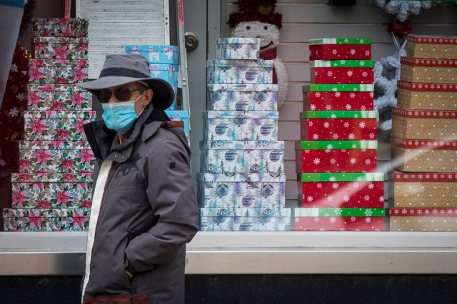 A person wears a mask as they walk past Christmas decorations in a store in Kingston, Ontario on Thursday, November 19, 2020, as the COVID-19 pandemic continues across Canada and around the world.